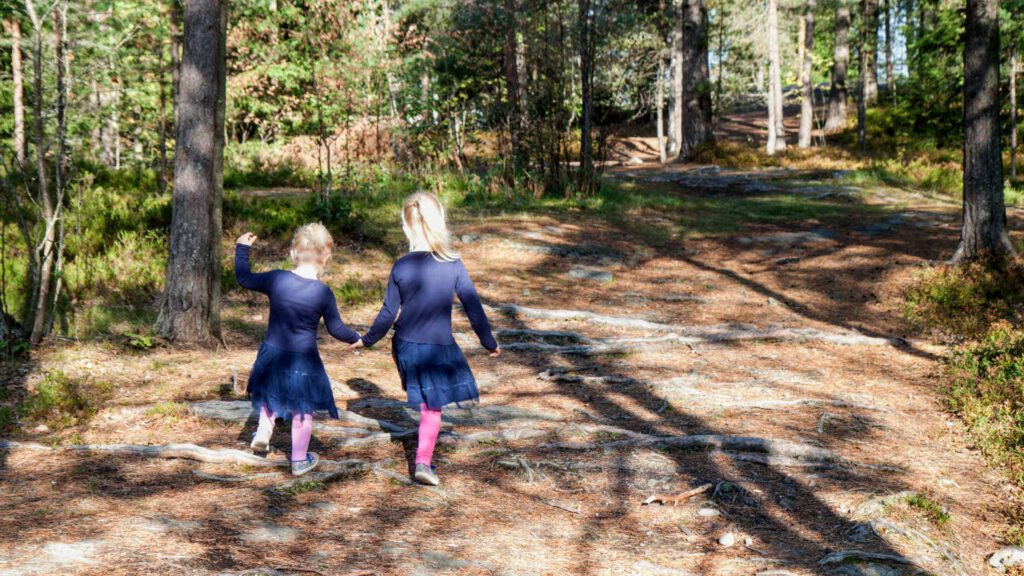 Tiny humans holding hands on a path