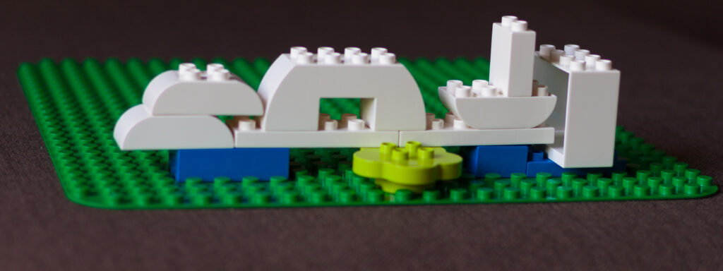 A bridge of white legos between scattered blue legos, held up by a flower block.