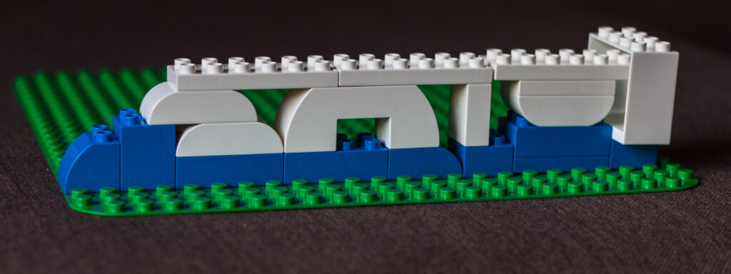White legos stacked on top of a blue line of legos.