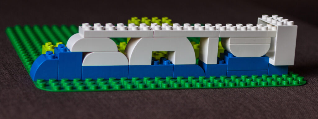 White legos stacked on top of a blue line of legos with some green legos behind them.